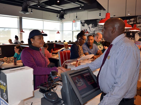 Steak 'n Shake manager Al Brown welcomes customer Makalen Coats of Canton to the restaurant.