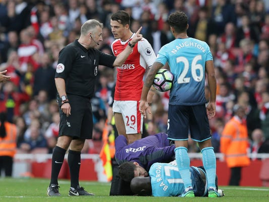 Arsenal's GranitXhaka, centre, is sent off by referee Jon Moss for a tackle on Swansea's Modou Barrow during the English Premier League soccer match between Arsenal and Swansea City at The Emirates Stadium in London, Saturday Oct. 15, 2016. (AP Photo/Tim Ireland)