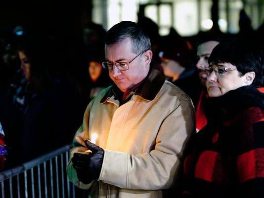 Washington State University President Kirk Schultz and his wife, Noel, attend a candlelight memorial service for Washington State quarterback Tyler Hilinski, Friday, Jan. 19, 2018, in Pullman, Wash. Hilinski, a sophomore, committed suicide earlier in the week. (Kai Eiselein/Moscow-Pullman Daily News via AP)