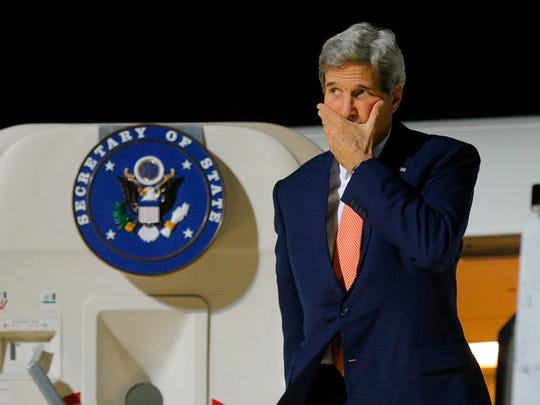 U.S Secretary of State John Kerry walks off his plane upon his arrival in Berlin, Tuesday, Oct. 21, 2014. Kerry is in Berlin to mark the upcoming 25th anniversary of the fall of the Berlin Wall. (AP Photo/Brian Snyder, pool)