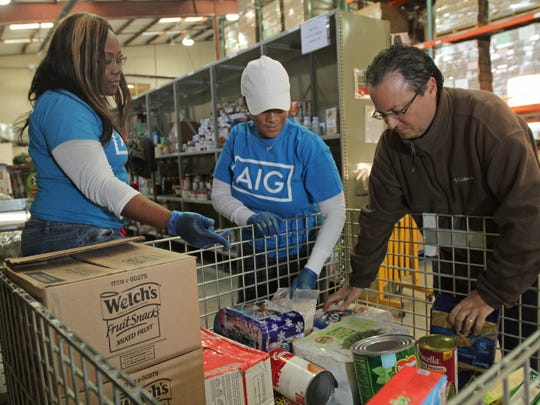 AIG volunteers Shareetah Beecher of Tinton Falls and Robin Wright of Neptune work with Asbury Park Press Reporter Jerry Carino as he volunteers for a day at the FoodBank of Monmouth and Ocean Counties.