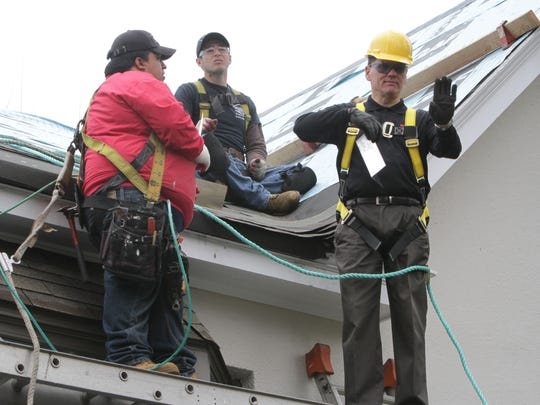 Wearing safety harnesses, workers Juan Illescas and