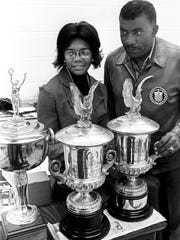 Tennessee State women's track coach Ed Temple, right, and one of the current Tigerbelle stars, hurdler Mamie Rallins, examine three trophies won by former Tigerbelle star Wilma Rudolph Oct. 26, 1971 and recently uncovered at a auction in St. Louis.