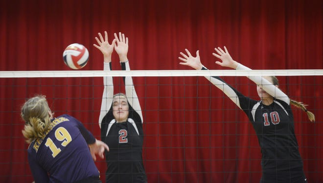 Manitowoc Lutheran's Kelly Herzog (2) and Lindsay Engelbrecht (12) try to block a shot from Kewaunee's Morgan Konop during the first set of Tuesday's WIAA regional tournament match.