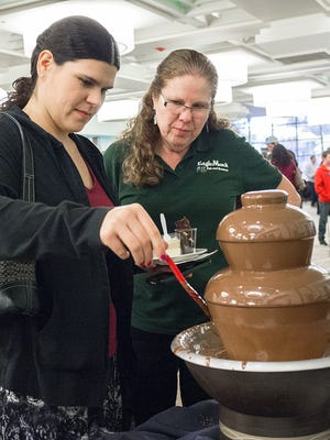 Megan Buonodono, dips a twizzler into a chocolate fountain while her mom Sonia waits her turn at the 27th Annual Chocolate Party Benefit Sunday, February 28, 2016.
