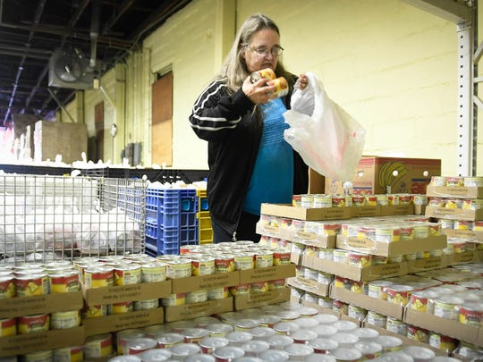 Tri-State Food Bank volunteer Belinda Higgs loads canned goods into take home weekend food bags for elementary students Friday, December 2, 2016.