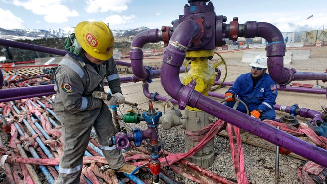 Workers tend to well equipment at a fracking site in Colorado in this 2013 photo.