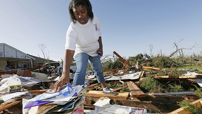 Tanisha Lockett searches through the remains of her aunt's child care business  in Louisville, Miss., Tuesday, April 29, 2014. The seven-year-old business was leveled among with a auto repair business next door and a private residence. Numerous businesses, residences and the community hospital were destroyed or heavily damaged after a tornado hit the east Mississippi community Monday. Louisville is the county seat and home to about 6,600 people. (AP Photo/Rogelio V. Solis)