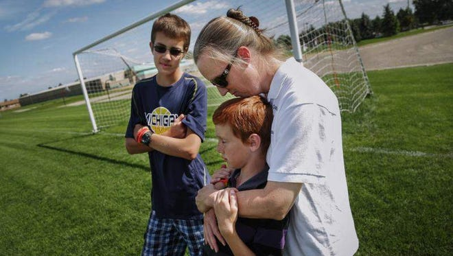 Kris Bieniewicz of Westland, seen with her sons Josh Bieniewicz, 9, and Kyle Bieniewicz, 14, says of the incident that led to her husband's death: 'We're not going to let the evilness that took place beat us. ... We're going to persevere through it.'