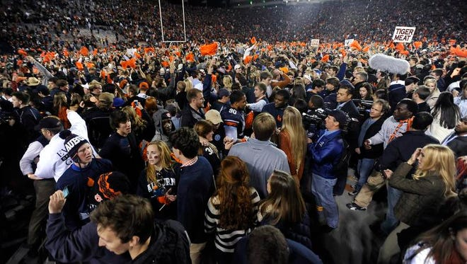 Auburn fans swarm the field after Auburn defeated Alabama in the Iron Bowl at Jordan-Hare Stadium in Auburn, Ala. on Saturday November 30, 2013.
