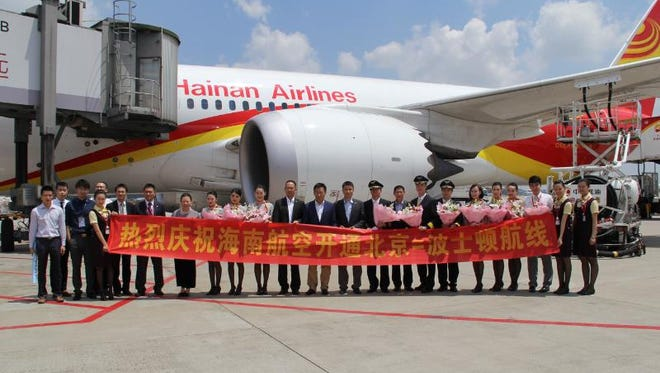 Hainan Airlines staff holds a banner commemorating the carrier's launch of service between Beijing and Boston.