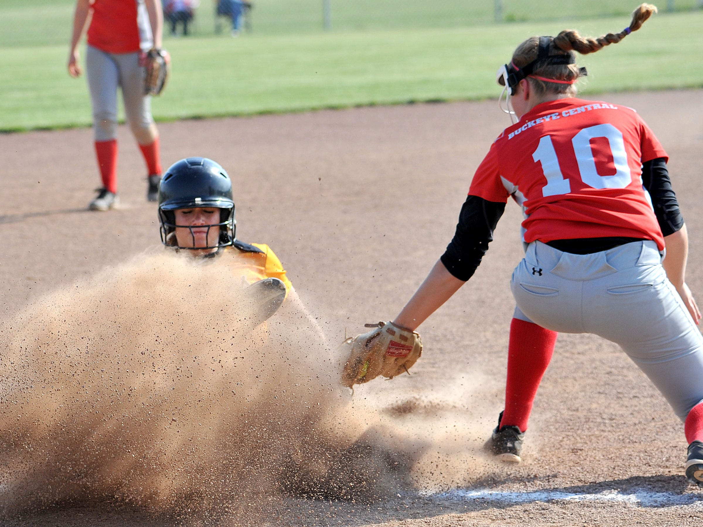 Colonel Crawford's Jada Klingenberger creates a massive dirt cloud as she slides safely to third base as Buckeye Central's Hailey Hildebrand attempts to tag her out during their game Wednesday evening.