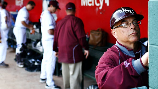 Missouri State head coach Keith Guttin makes annotations in the home team dugout during the Bears' 2015 home opener game against the University of Arkansas at Little Rock.