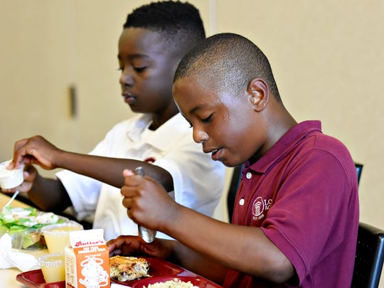 Fifth graders Alex Hardy, front, and Da'Nas Edwards eat lunch at Logos Academy in York City, Monday, Aug. 29, 2016. Dawn J. Sagert photo