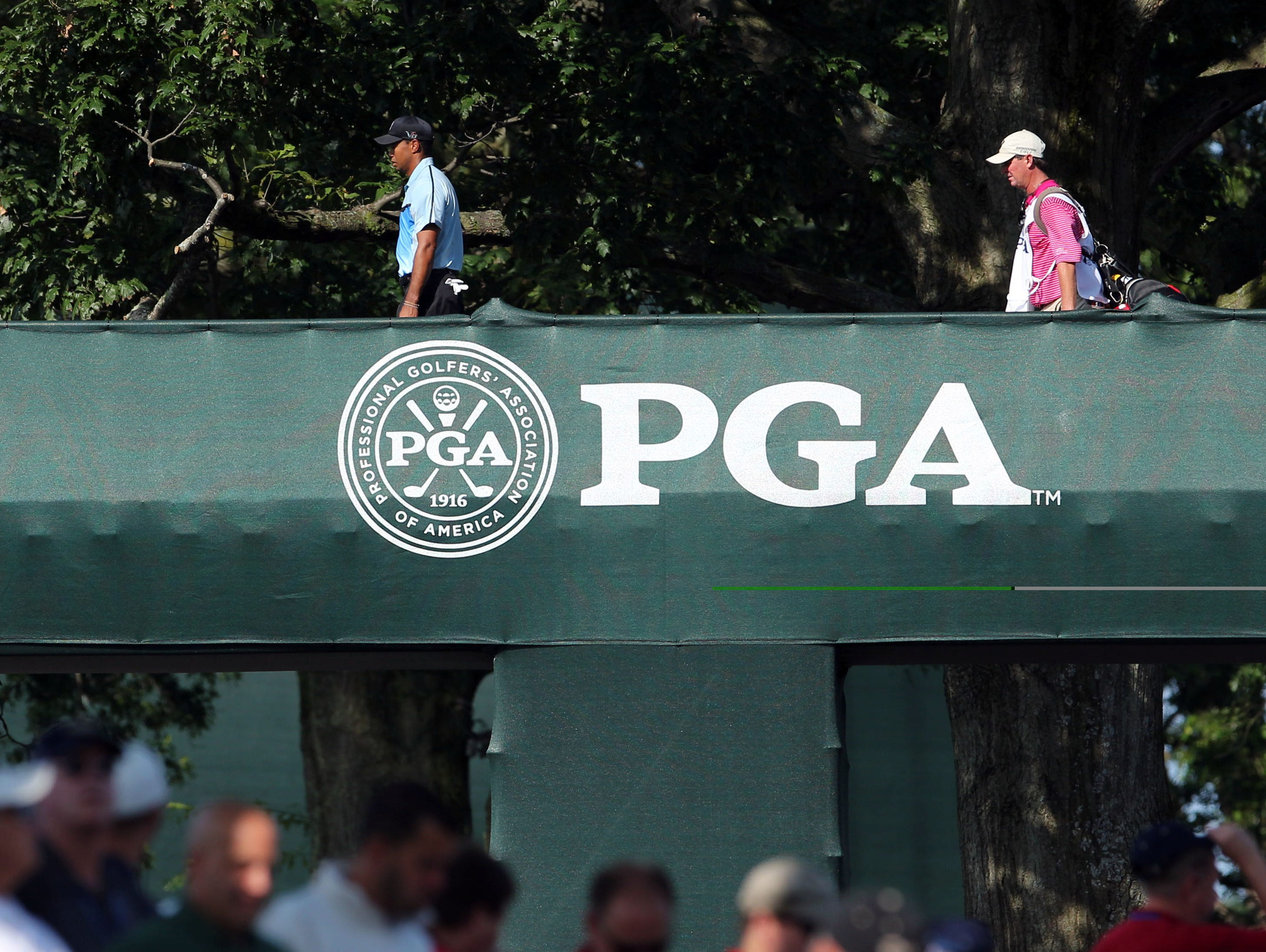Tiger Woods walks over the players bridge during the first round of the 95th PGA Championship at Oak Hill Country Club.