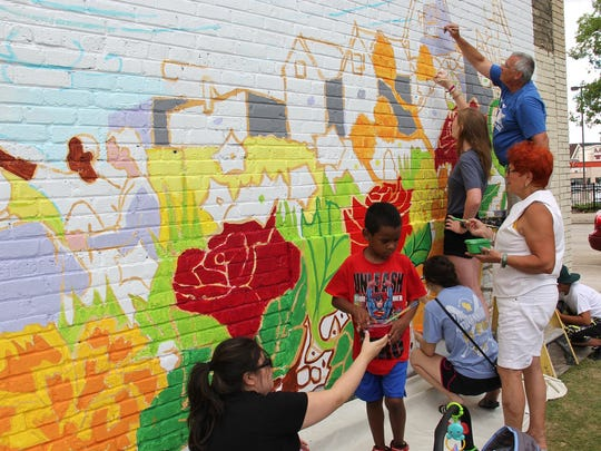 Community members fill in the outline of a mural painted on the wall of EL Rey by Tia Richardson, Jeanette Martín and Randy Flann.