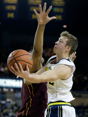 Michigan's Spike Albrecht goes to the basket against Minnesota's Maurice Walker during the first half.