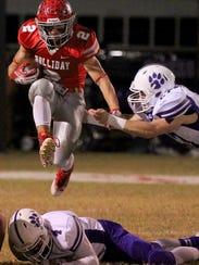 Holiday's Justin Jones hurdles Jacksboro's Caleb Keith