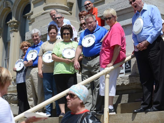 Participants watch as Cindy Cameron braces herself for a pie in the face during the Operation Feed wrapup event outside the Muskingum County Courthouse in Zanesville on Tuesday.