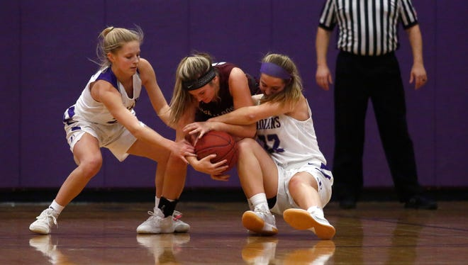 Indianola senior Allison Coffey and sophomore Kenall Clatt try to wrest the ball away from Oskaloosa sophomore Jillian Jennings. Indianola beat Oskaloosa 60-19 in a Little Hawkeye Conference game in Indianola on Jan. 4.