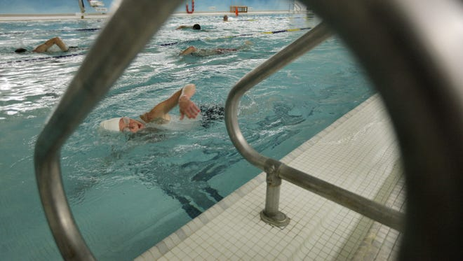 Therese Christo of Hilton, during the 15-minute pool swim before the next two events, the 15-minute stationary bike ride and the 15-minute indoor track run or walk, during YMCA indoor triathlon at the Carlson Metrocenter in Rochester in 2011.