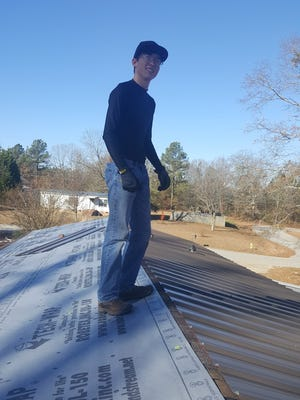 Alex Clarke, a Belton-Honea Path High School student who works part-time at Anderson Metal Supply over winter break from school, helped install a roof last week in Pelzer.