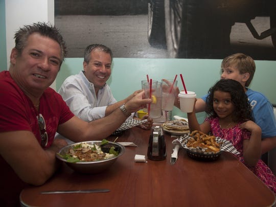 Chris Schwam (from left) and Steven Piacquadio, with their kids Nicolas Schwam-Piacquadio and Alexa Schwam, enjoy eating at the Pop Shop in Collingswood often. The popular comfort-food restaurant celebrates its 10th anniversary this month.