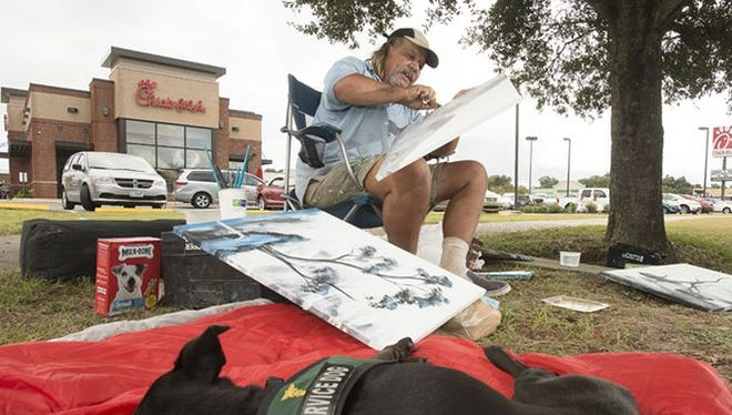 Homeless artist Jon Masters works on his artwork while sitting on the side of Navy Blvd. Tuesday morning while his service dog, Sheba, sleeps.