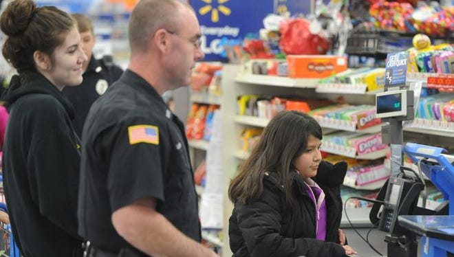 Officer John Lackey, foreground, helps children as part of the FOP Lodge 63's Shop with an Officer program in December at Walmart. About 25 children shopped for clothes and toys for the holidays with Richmond Police Department and Wayne County Sheriff's Department officers.