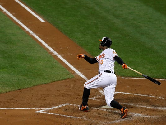 Baltimore Orioles' Adam Jones hits a sacrifice fly ball in the third inning of a baseball game against the Boston Red Sox in Baltimore, Wednesday, Sept. 21, 2016. Jonathan Schoop scored on the play. (AP Photo/Patrick Semansky)