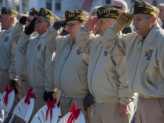 Veterans, representing Gen. George S. Greene VFW Post 761 in Dumont, salute the American flag at the ceremony.