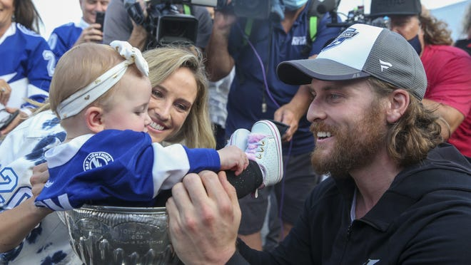 Blake Coleman of the Tampa Bay Lightning places his 7-month-old daughter Charlie in the Stanley Cup as Coleman's wife, Jordan, looks on. Coleman is a former St. Mary Catholic Central student.