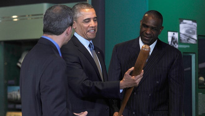 President Barack Obama, accompanied by Baseball Hall of Fame President Jeff Idelson, left, and 2010 inductee Andre Dawson, holds Babe Ruth's bat during a tour the Baseball Hall of Fame in Cooperstown, N.Y., on Thursday.