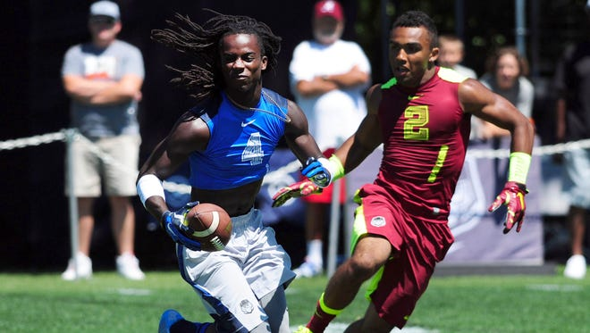 Land Sharks cornerback Donte Jackson (4) returns an interception as Vapor Carbon wide receiver Christian Kirk (2) gives chase during Nike Football ' The Opening' at Nike World Headquarters.