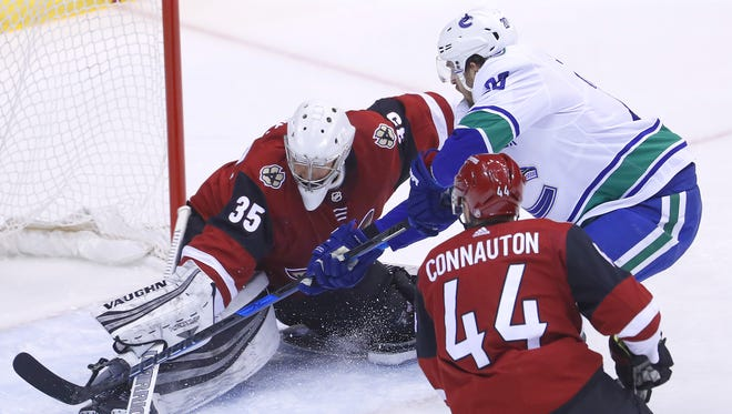 Coyotes' Darcy Kuemper (35) makes a save on a shot from Canucks' Brandon Sutter (20) during the first period at Gila River Arena on February 25, 2018 in Glendale, Ariz.
