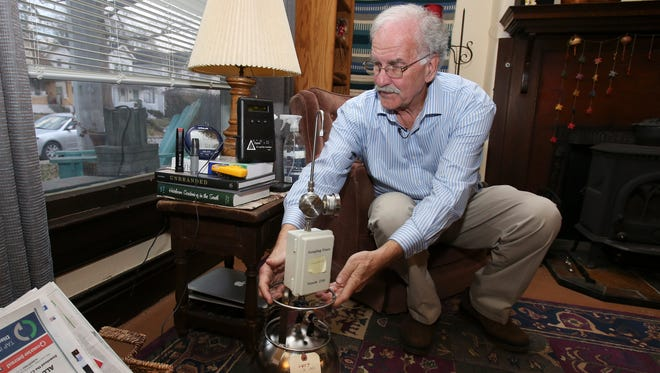 Russ Barnett, director of the Kentucky Institute for the Environment and Sustainable Development at the University of Louisville, places devices designed to measure air quality in the home of Courier-Journal environmental reporter James Bruggers.Feb. 16, 2017