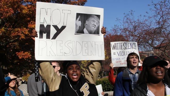 "A student holds a sign that reads, ""Not my president,"" with a picture of President-elect Donald Trump on it. Purdue University community members held a ""Love Trumps Hate"" rally on campus Wednesday, Nov. 16, 2016."