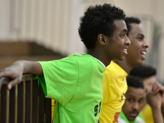 The Dream Team's Ismail Abdi, 20, smiles as he and his friends watch another game Saturday during the St. Cloud Somali Youth Organization Basketball Tournament at Apollo High School.