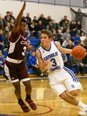 Catholic Central's Gio Genrich (right) makes the dribble