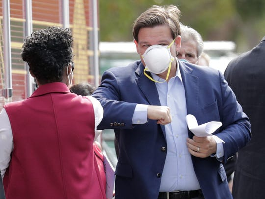 Florida Gov. Ron DeSantis, right, elbow bumps an official as he arrives for a news conference at the Urban League of Broward County, during the new coronavirus pandemic, Friday, April 17, 2020, in Fort Lauderdale, Fla.