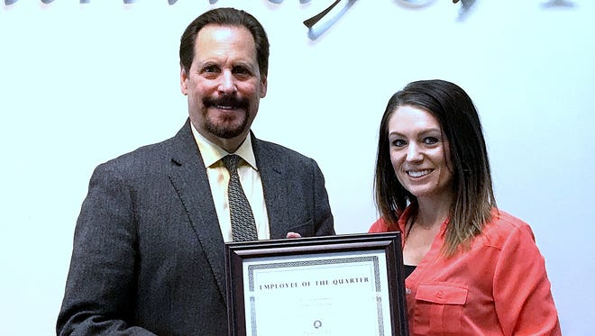 Pathways Inc. employee Christie Glick accepts the employee of the quarter certificate from President and CEO Edward Lukomski.