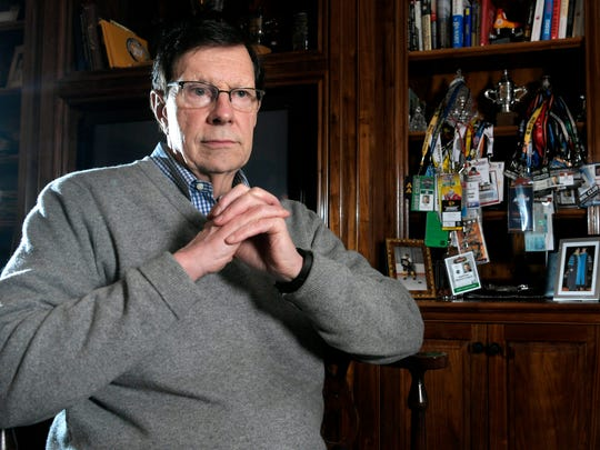 David Poile sits in his office of his Nashville home where many game day and special event passes hang from a shelf along with many of his hockey awards and photographs of his family.
