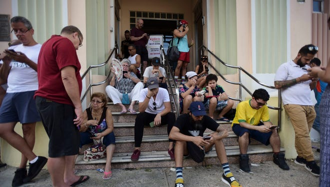 People congregate at a wifi hotspot in the aftermath of Hurricane Maria with many cellphone towers down in San Juan, Puerto Rico, Sunday, Sept. 24, 2017.