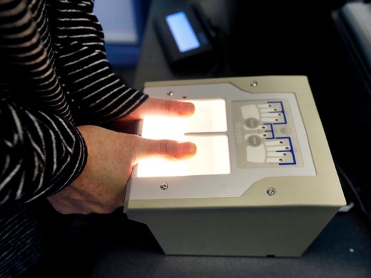 Finger prints are taken electronically for background checks and can be viewed on the computer screen while IdentoGo records the information. Photo taken on Tuesday, Jan. 30, 2018.
