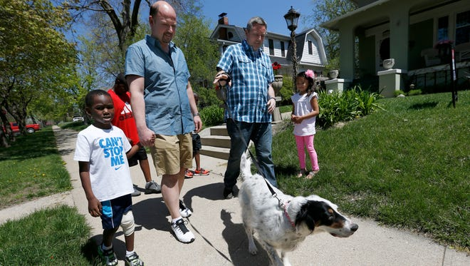 Chuck and Jason Swaggerty-Morgan take their family for a walk around their neighborhood April 26, 2015, in Sioux City, Iowa.