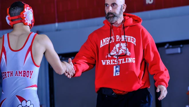 Perth Amboy wrestling head coach Mike Giordano congratulates a wrestler after a bout during the NJSIAA North 2 Group V quarterfinals in Perth Amboy on Feb. 6, 2017.