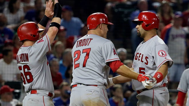 Los Angeles Angels' Kole Calhoun (56), Mike Trout (27) and Albert Pujols, right, celebrate the three-run home run by Pujols that came off a pitch from Texas Rangers relief pitcher Jeremy Jeffress in the eighth inning of a baseball game in Arlington, Texas, on Friday.