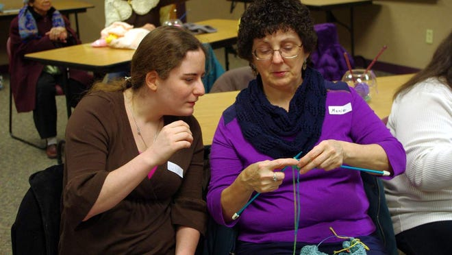 Kim Vissa, left — who was brand-new to the group and to knitting — gets instruction from longtime Sit & Stitch group member Marie Ferner.