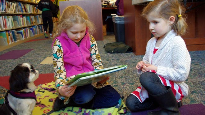 Mila, 7, at left, and Etta Sorensen, 4, of Brighton read to Annie, a 4-year old Shih Tzu at the Brighton library.