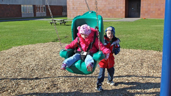 Schlegel's Jacob Griffin pushes his little sister Anna on a swing at the playground.